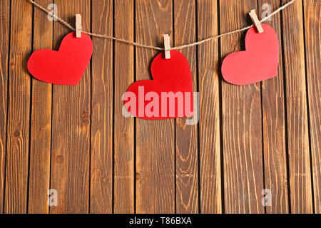Paper hearts hanging on rope against wooden background - Stock Photo