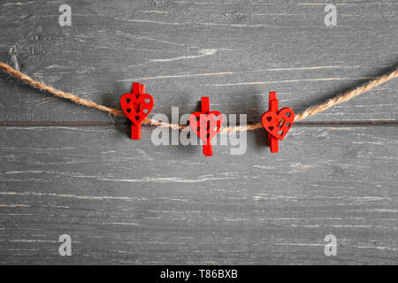 Pegs with hearts hanging on rope against wooden background - Stock Photo
