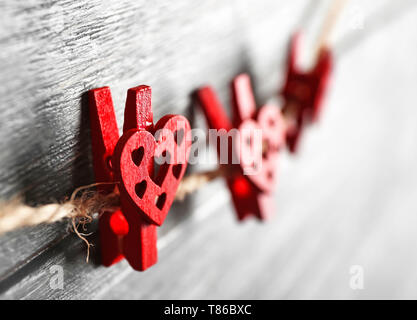 Pegs with hearts hanging on rope against wooden background, closeup - Stock Photo