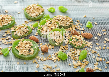 Raw oatmeal, dried kiwi and almond on wooden background - Stock Photo