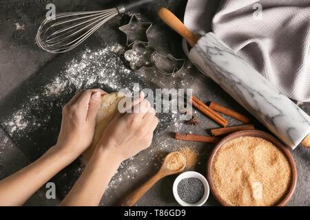 Woman kneading dough on table - Stock Photo