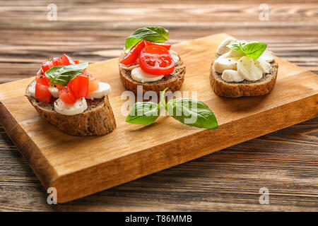 Tasty sandwiches with mozzarella, tomato and basil on wooden board - Stock Photo