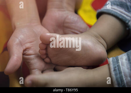 Close up Mother Holding Feet of infant Baby in Her Hand - Stock Photo