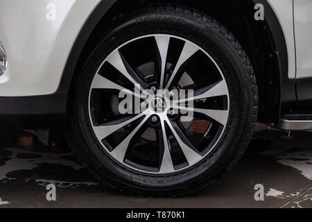 Novosibirsk, Russia - 05.10.2019: Front wheel view of Toyota RAV4 2015 year in white color after cleaning before sale on parking. Auto service industr - Stock Photo