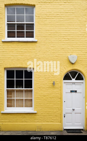 Colourful yellow painted house in Godfrey street, Chelsea, London, England - Stock Photo
