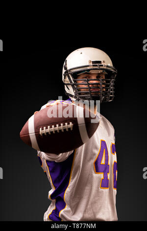 American football player holding the ball in his hands in front of the camera. Concept American football, motivation, black background - Stock Photo