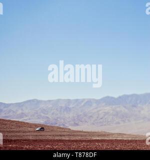 Automobile Driving Through Desert - Stock Photo