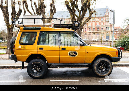 Strasbourg, France - Dec 27, 2017: Side view of Vintage new yellow Land Rover Defender Camel Trophy with luggage on the roof parked in central city street with - Stock Photo