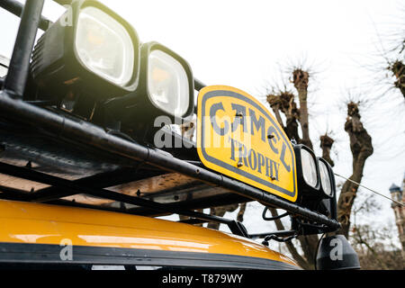 Strasbourg, France - Dec 27, 2017: Detail of the roof light and insignia vintage yellow Land Rover Defender Camel Trophy with luggage on the roof parked in central city street with - Stock Photo
