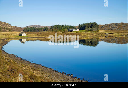 Stack Lodge on the Reay Forest estate seen from Loch Stack, Sutherland, Scottish Highlands UK, beautiful calm spring morning, reflections on loch. - Stock Photo