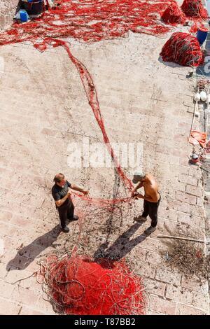 Italy, Sardinia, Oristano Province, Bosa, fishermen disentangling a net - Stock Photo