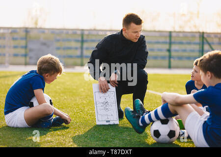 Football coach coaching children. Soccer football training session for children. Young coach teaching kids on football field. Football tactic educate - Stock Photo