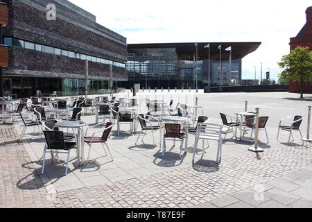 10 May 2019: Cardiff Bay, Cardiff UK:  Sets of chairs sit out in the sunlight alongside Wales Millennium Centre and the National Assembly for Wales. - Stock Photo