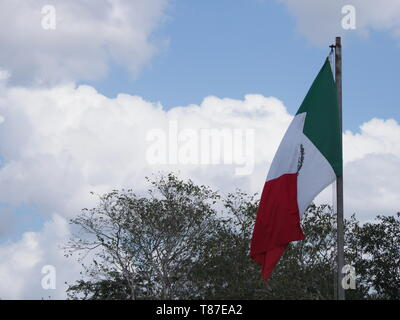 National maxican flag at beautiful Chichen Itza city near archaeological site in Mexico with trees and cloudy blue sky - Stock Photo
