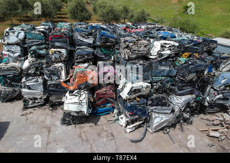 Cars in junkyard, pressed and packed for recycling. - Stock Photo