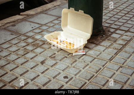 Extra food waste and scraps with and a rest of the cigarette in plastic box thrown in the city street. Pollution of the environment - Stock Photo