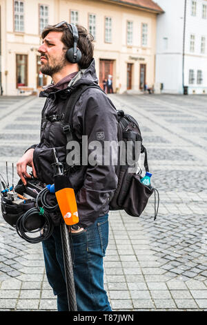 Sibiu City, Romania - 9 May 2019. lateral view of a television technician sound recording outdoor on the street maintaining a ladder - Stock Photo