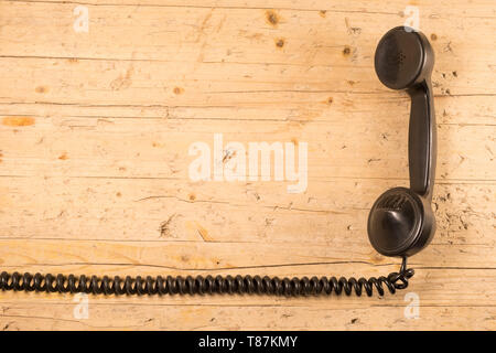 old telephone handset of the early twentieth century isolated with its elastic twisted cord on old wooden background - Stock Photo