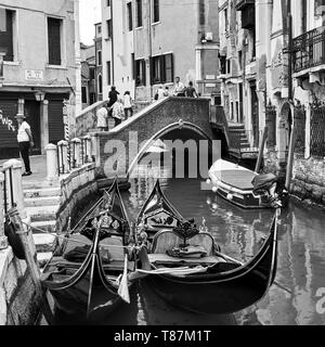 Venice, Italy - June 18, 2018: Two gondolas on canal near small bridge in waiting of tourists. Black and white image - Stock Photo