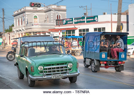 Santa Clara, Villa Clara, Cuba-May 5, 2019: Transportation in the Caribbean island. Old green car drives in the Central road. A rickshaw goes in the o - Stock Photo