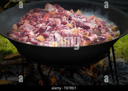 sliced meat cooked on a very large pot for a very big crowd - Stock Photo