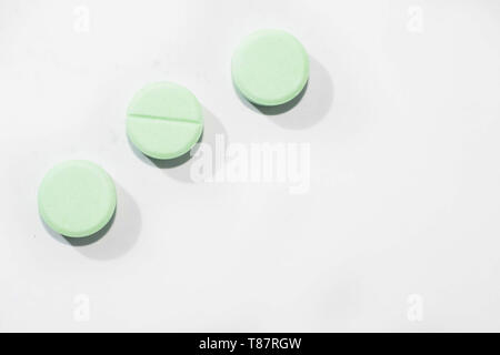 Three round green pills arranged diagonally on a white background - Stock Photo