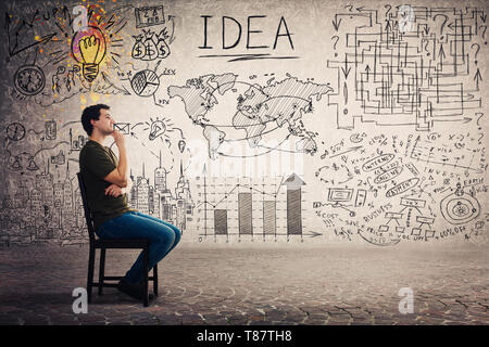Side view of casual guy seated on a chair keeps hand under chin thoughtful looking away, has a lot of plans and goals as business sketch on grey backg - Stock Photo