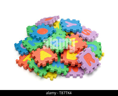 Pile of colorful foam alphabet puzzle pieces isolated on white - Stock Photo