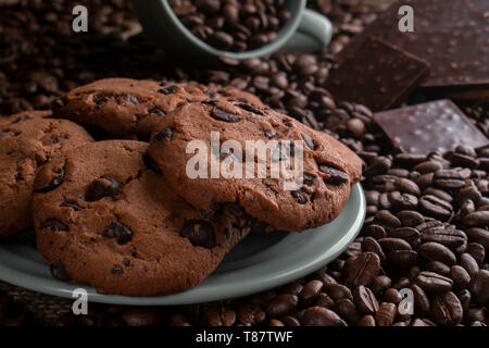 on coffee beansthe cup lies from it gets enough sleep coffee, opposite a chocolate bar, there are cookies behind - Stock Photo