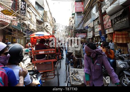 Narrow streets of Chandni Chowk in Old Delhi, rickshaws and motorcycles and congested street traffic. - Stock Photo