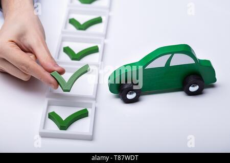 Human Hand Placing Check Mark Icon Near Small Green Car - Stock Photo
