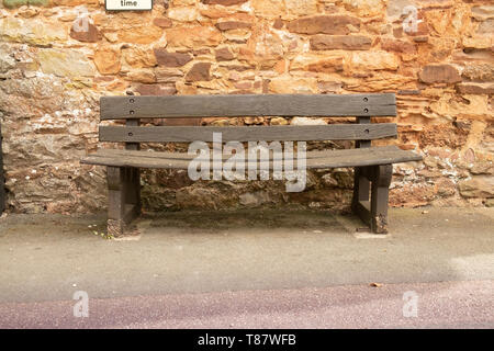 Worn, bent, empty wooden bench in the village of Cockington,Devon,England,UK - Stock Photo