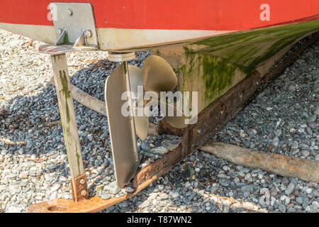 Back of a traditional fishing boat showing the propeller and rudder,  on the beach in the small fishing village of Cadgwith,Cornwall, England,UK - Stock Photo