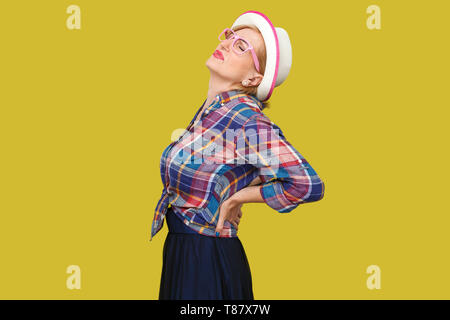 Back, spine or kidney pain. Profile side view portrait of modern stylish mature woman in casual style with hat standing and holding her painful back.  - Stock Photo