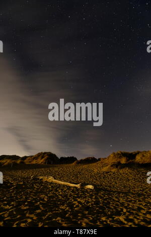 Sand sunes and a washed up tree trunk are lit up by ambient light against a starry sky with the plough visible Croyde beach Devon - Stock Photo