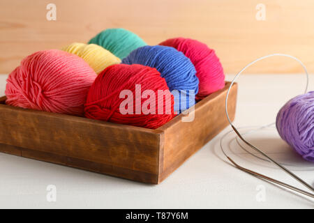 Box with balls of knitting yarn and needles on light table - Stock Photo