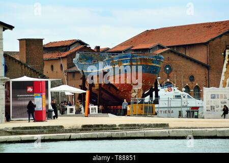Venice, May 7th, 2019 : the relict of the fishing boat,that, sank near the isle of Lampedusa in 2015, where more than 700 migrants died, was recovered by the Italian government, and was given to the town of Augusta, Sicily. The Suiss artist Christoph Buchel shipped it to Venice and exhibits the relict at the Venice Arsenale, for the 58th Biennale d'Arte di Venezia. 'Barca Nostra' (English : Our Boat) is the title of the artistic installation. The 58th Biennale title is 'May You Live in Interesting Times' The exhibition will open from May 11th to November 24th 2019. - Stock Photo