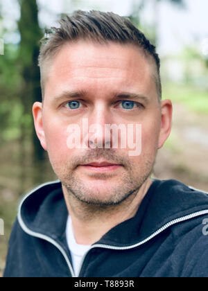 Handsome blue eyed mid adult caucasian close up up face portrait outdoors with forest background - Stock Photo