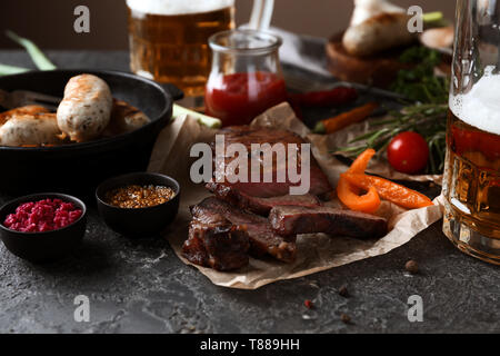 Glass of delicious beer with grilled steak and sausages on grunge table - Stock Photo