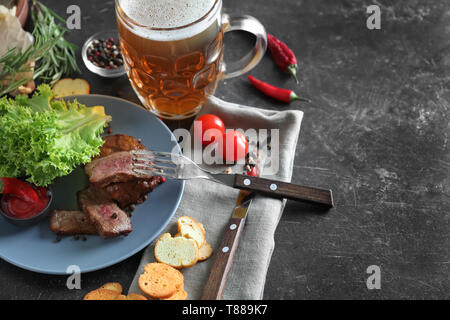Mug of delicious beer with grilled steak and spices on grey table - Stock Photo