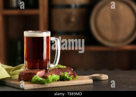 Mug of delicious beer with grilled steak on table - Stock Photo