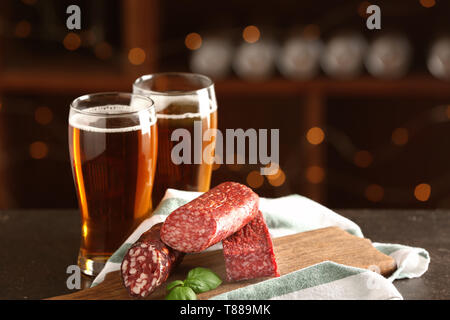 Glasses of delicious beer with smoked sausages on table - Stock Photo