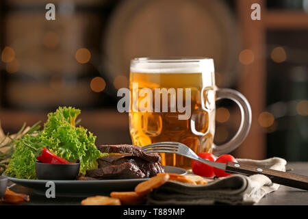 Mug of delicious beer with grilled steak and sauce on table - Stock Photo