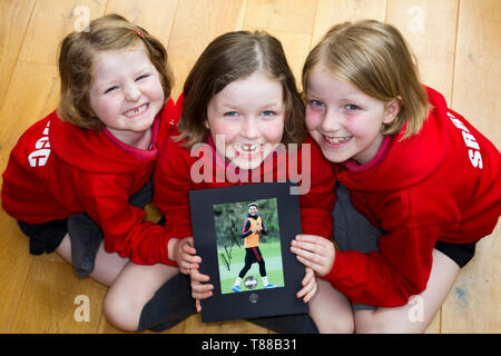 Three football fan / fans / primary school girls / children / kids with a signed autograph photograph of Manchester United & England soccer player Jesse Lingard. - Stock Photo