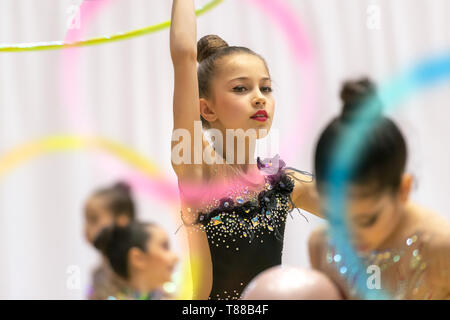 Portrait of a little pretty girl trying to win the rhythmic gymnastics championship, dancing with a hoop and wearing beautiful leotard embroidered wit - Stock Photo