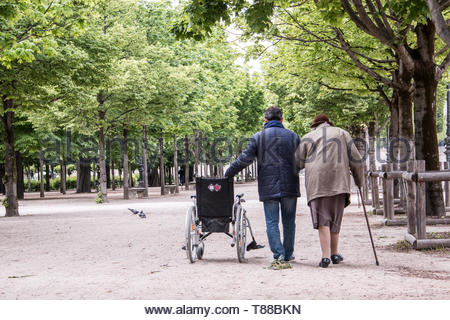 Paris (France), May 6, 2019. Elderly accompanied person taking a walk in the Tuileries gardens, near Louvre in Paris. - Stock Photo