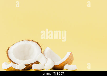 close up fresh coconut pieces isolated on a yellow background, tropical fruit concept, flat lay, pop art, copy space. - Stock Photo