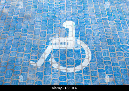 Top view on parking sign for disable people. Disabled parking space and wheelchair symbols on pavement. - Stock Photo
