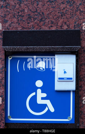 Handicapped access entrance pad mounted to a wall. Sign a button for a visa for people with disabilities. - Stock Photo