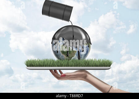 Female hand holding earth globe covered with black thick liquid from black oil barrel on green grass model on blue sky background - Stock Photo